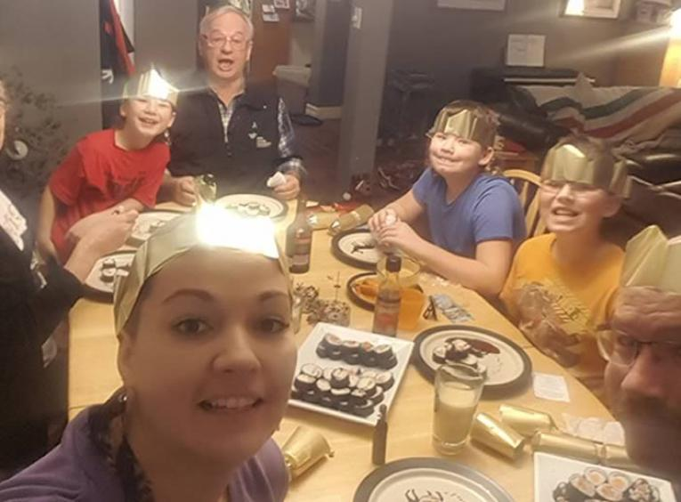 7 people around a dinner table wearing paper crowns.