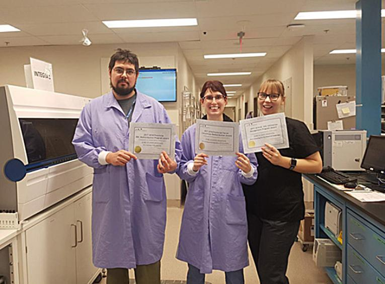 The lab technologist team standing with the certificate awards.