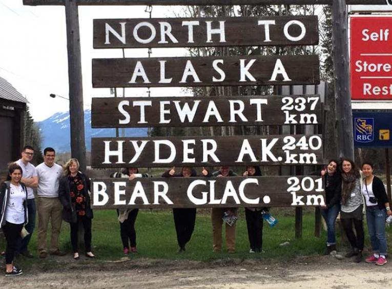Group standing below a big wooden sign showing towns.