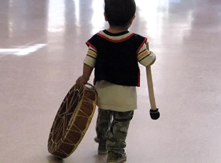 Young boy carrying drum