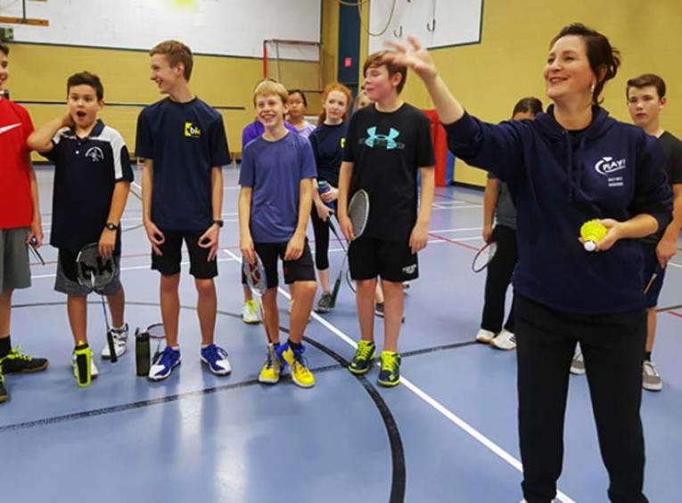Woman tosses a badminton birdie in a gymnasium as a group of young students watches.