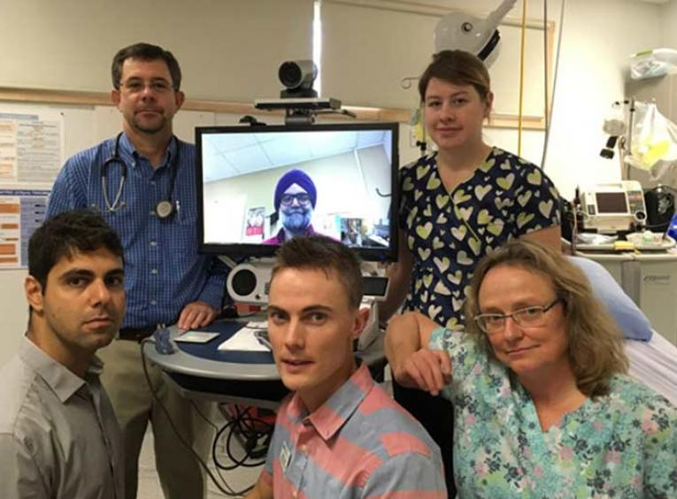 Health care providers posing with a telehealth system.