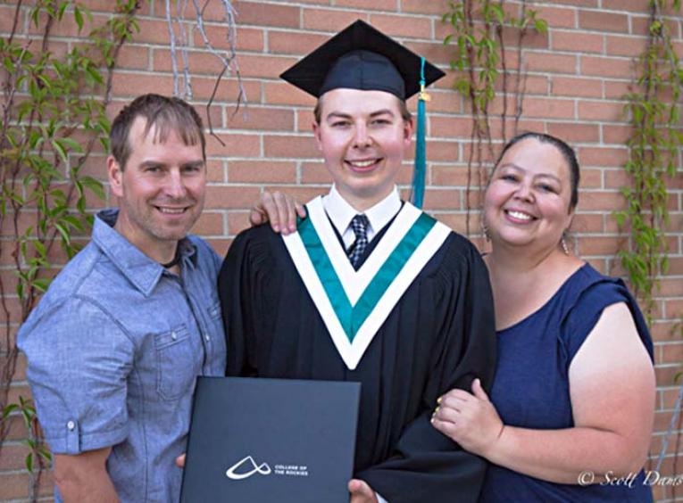 Man standing with his parents posing at graduation.