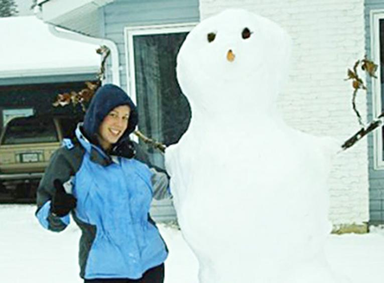 Snowman standing beside woman.