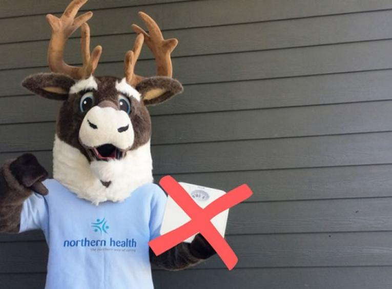 Spirit the caribou mascot holding scale