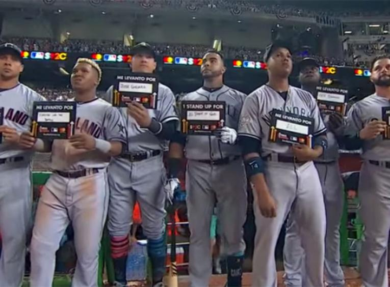 MLB Baseball players in a row during game night while holding stand up to cancer placards.