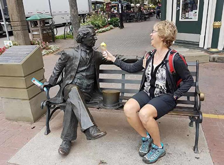 susan Knoll sitting on a bench with a statue, eating ice cream.