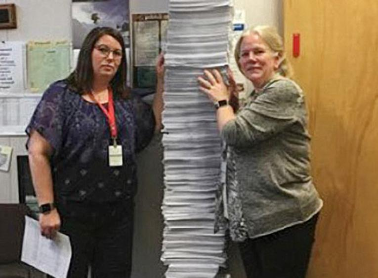 Two women standing with a tall stack of chart copies between them.