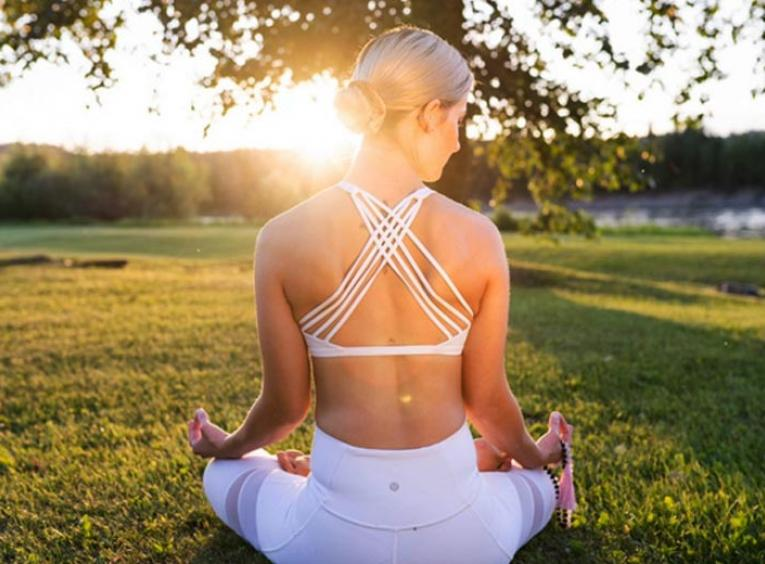 Woman practising yoga, sitting cross-legged on grass with her back to the camera. The sun sets in the horizon, over her left shoulder.