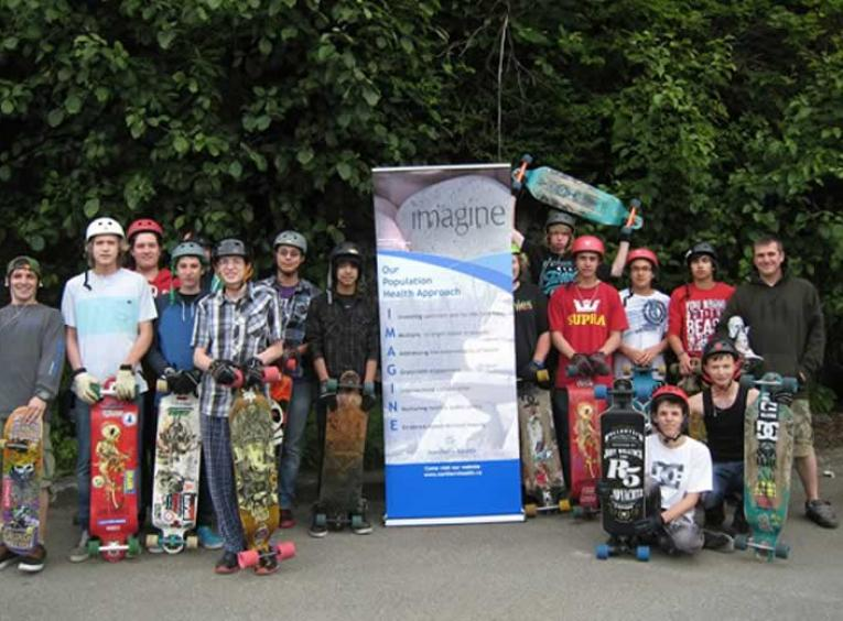 Large group of youth standing with skateboards and wearing helmuts.