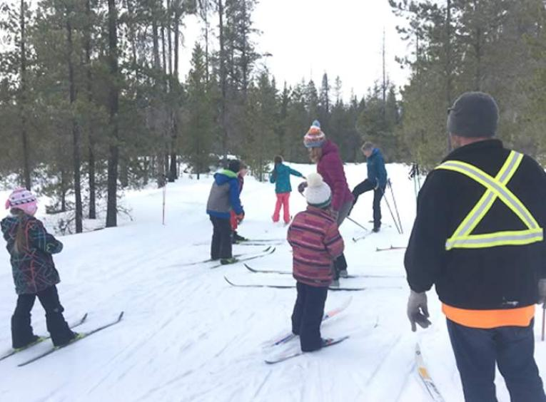 Group of kids, wearing bright jackets and hats, cross country skiing.