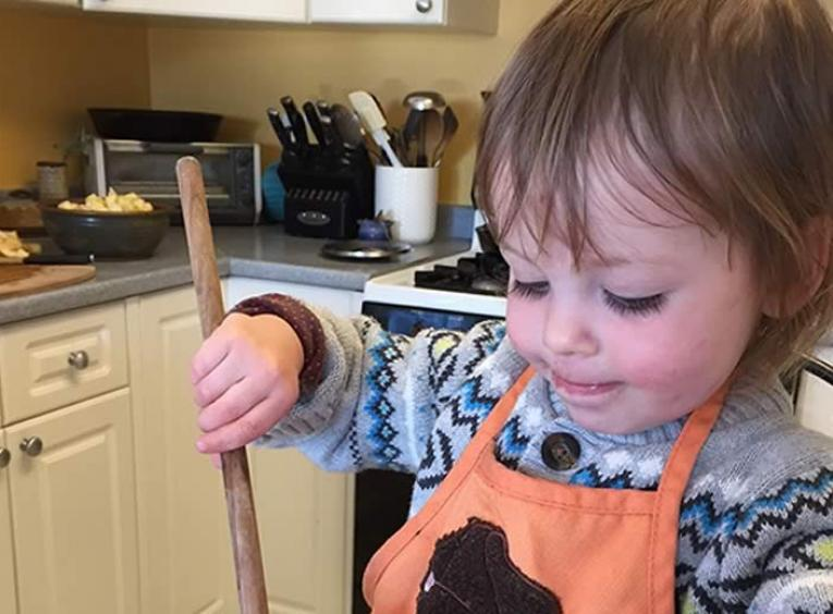 Toddler holding a wooden mixing spoon over a bowl full of oats.