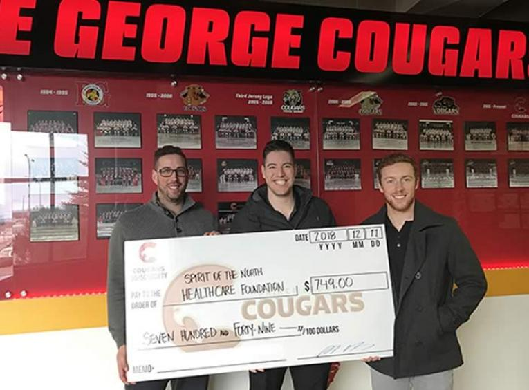 Three men holding a large cheque in front of a red sign Prince George Cougars.
