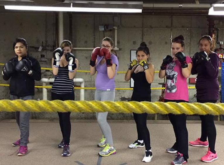 Group of 5 female teens in a boxing ring wearing boxing gloves.