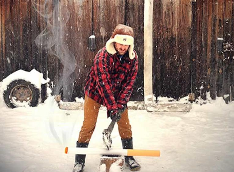 Man wearing a plaid jacket and hat outside in the snow chopping a large pretend cigarette.