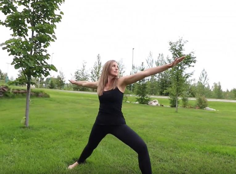 Girl doing a yoga pose on a grassy field.