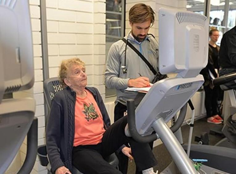Patient on exercise bicycle monitored by physiotherapist.