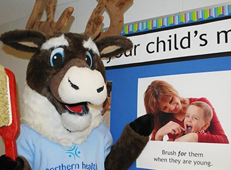 Spirit the caribou mascot holding a giant red toothbrushin front of poster