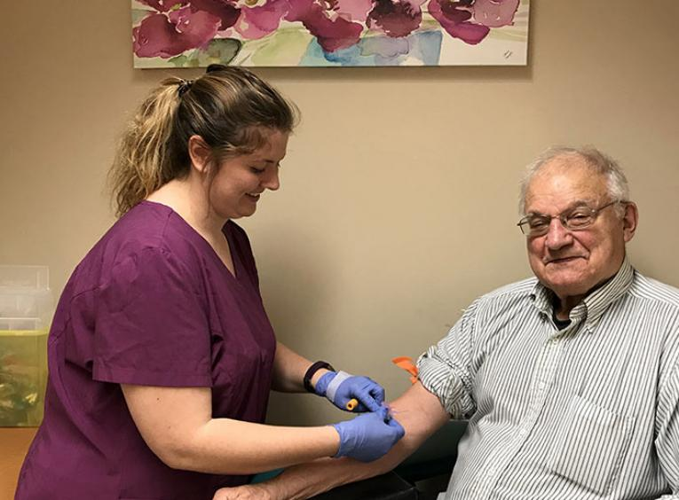A woman draws blood from an elderly man.