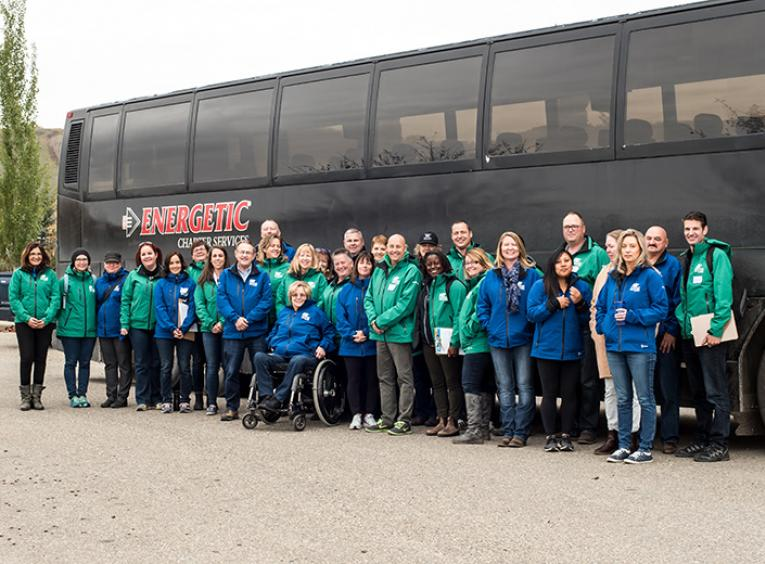 A large group of people in blue or green BC Winter Games jackets stand in front of a bus.