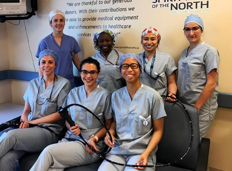Seven nurses smile into the camera, holding a pediatric colonoscope.