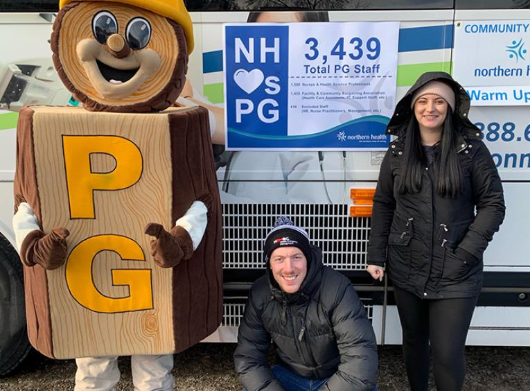 The Mr. PG mascot stands with a crouching man and a standing woman next to the NH Connections bus.