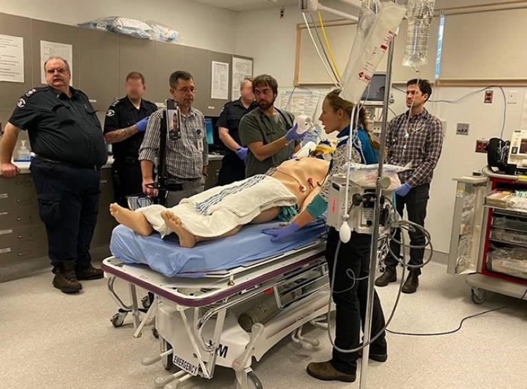 A group of paramedics and health care professionals stand in a medical room around a simulation mannequin.