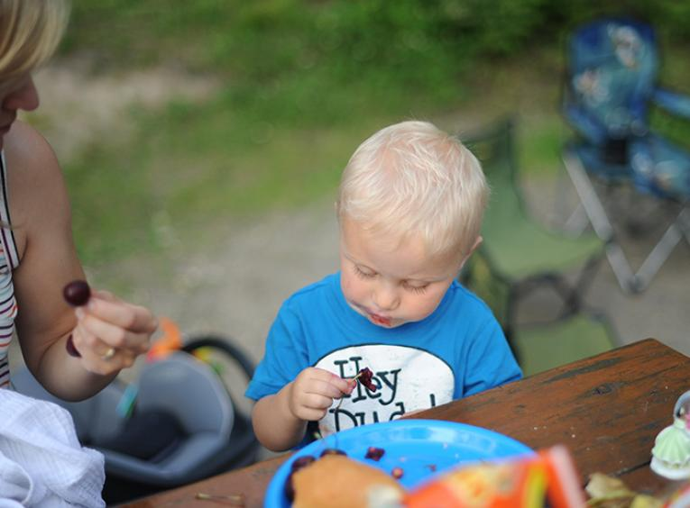 A toddler boy looks at a cherry he is eating at a picnic table while his mom looks at him.