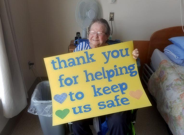"A female long-term care resident holds a sign that says, ""thank you for helping to keep us safe."""