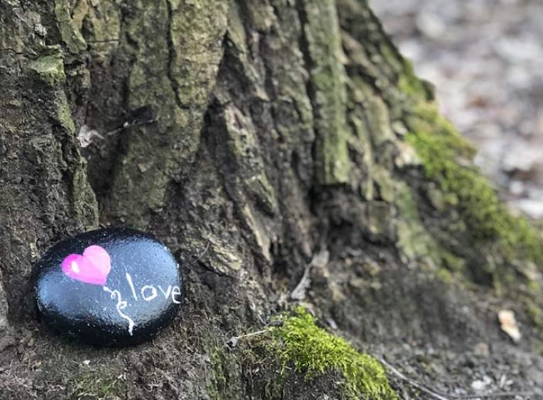 "A small rock with a heart-shaped balloon and the word ""love"" painted on it lays against the base of a tree."