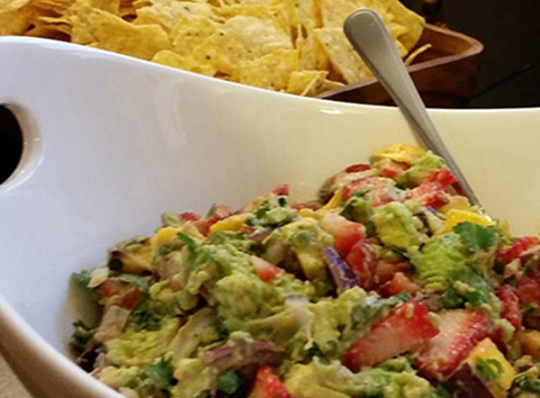 Strawberry mango guacamole in a white bowl, with spoon, and chips in background
