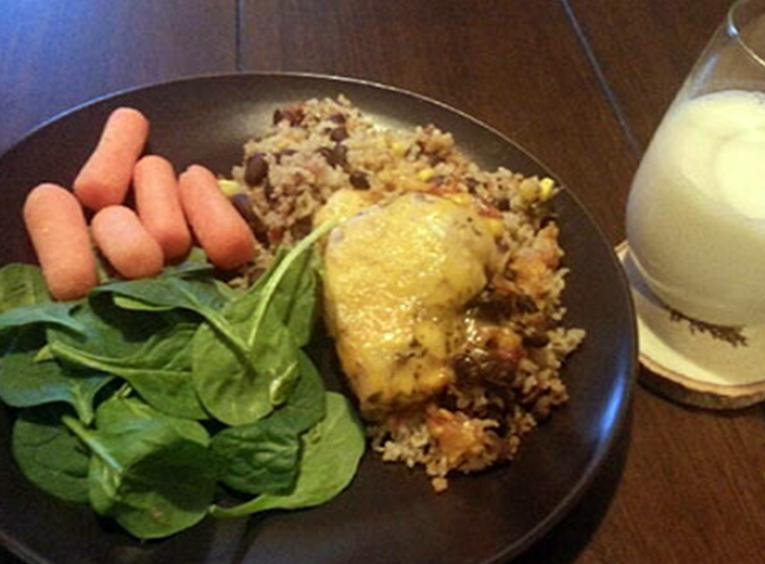 Chicken casserole with spinach, carrots and wild rice on a plate, served with a glass of milk