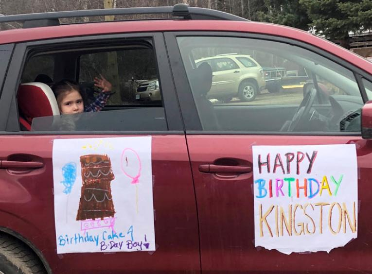 A young girl waves out the back of a red SUV decorated with homemade posters featuring birthday wishes.