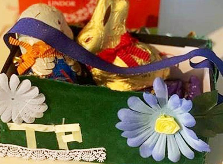 A green homemade Easter basket has the initials TP on it, as well as decorative blue and pink flowers.