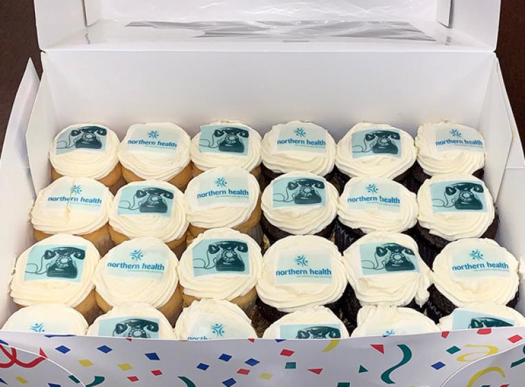 A box of cupcakes that are decorated with the Northern Health logo and pictures of old phones.