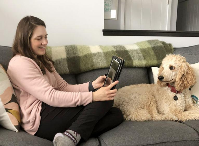 A young woman sits on a couch, chatting to another person on a tablet. A poodle sits on the other side of the couch.