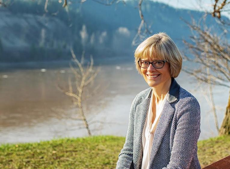 A woman smiles into the camera, a river behind her.