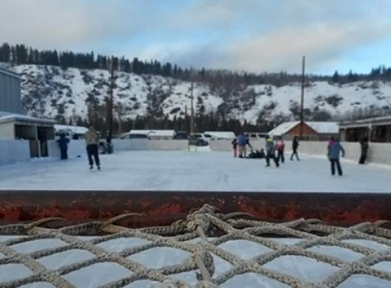 People skating on an outdoor ice rink.