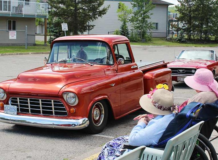 An old red pickup truck drives past two women in wheelchairs.