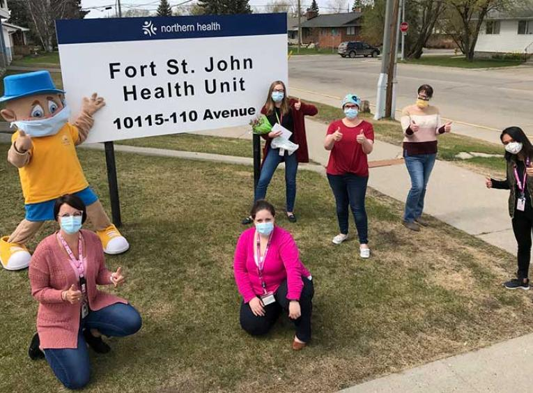 Six nurses and a mascot pose, wearing masks and giving thumbs up signs, outside the Fort St. John Health Unit.