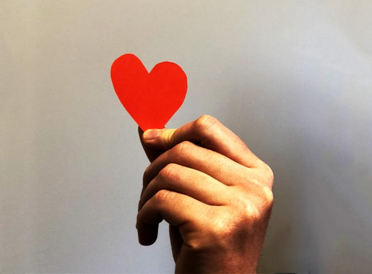 A hand holds a red construction paper heart.