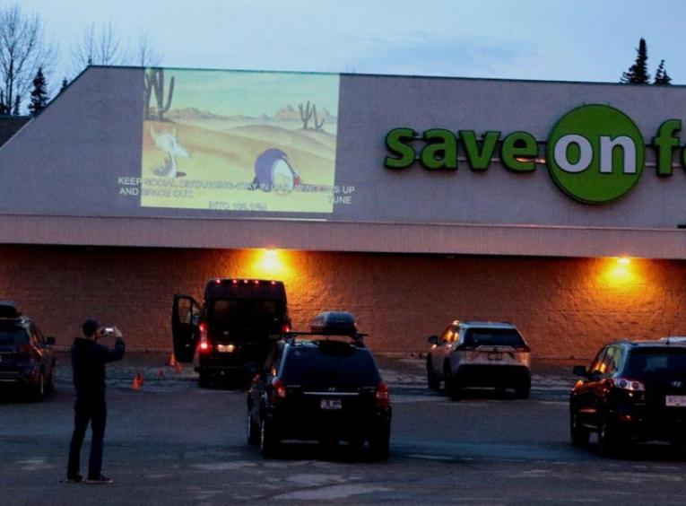Cars are parked in a Save On Foods parking lot, a cartoon is projected on the wall.