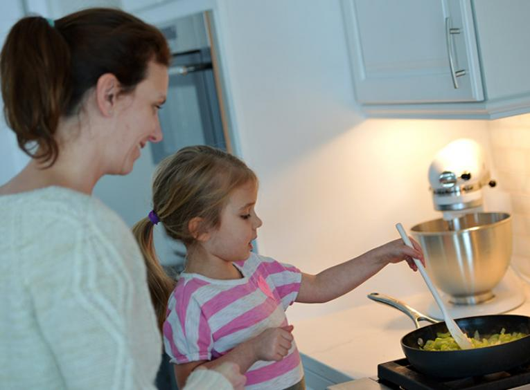 In a kitchen, a woman holds a young girl who stirs food in a pan on the stove.