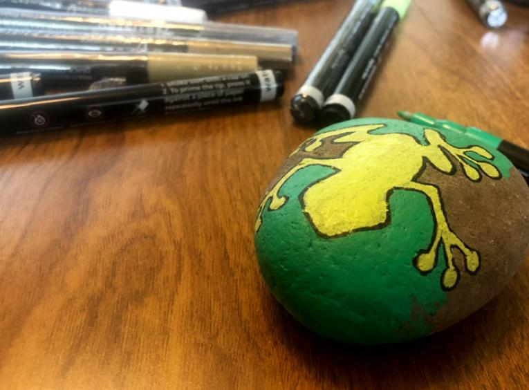 A rock has a yellow frog painted on it.