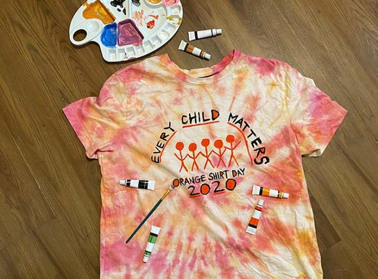A tie-dye orange t-shirt decorated with paints for Orange Shirt Day 2020.