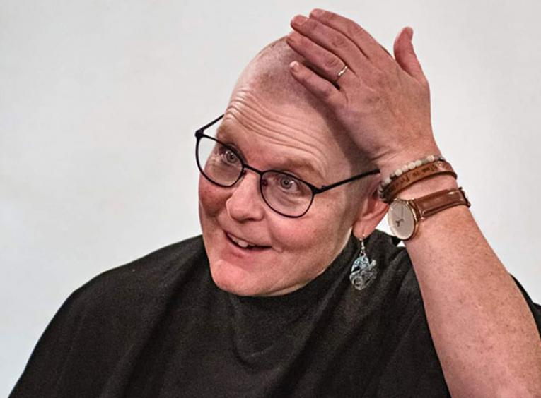 Woman with glasses touches head after having it shaved