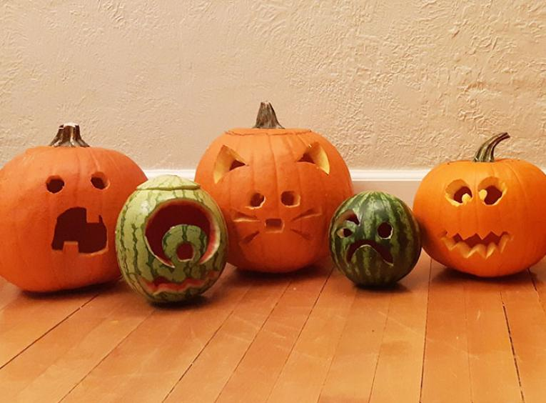 A row of carved jack-o-lanterns sitting on the floor.