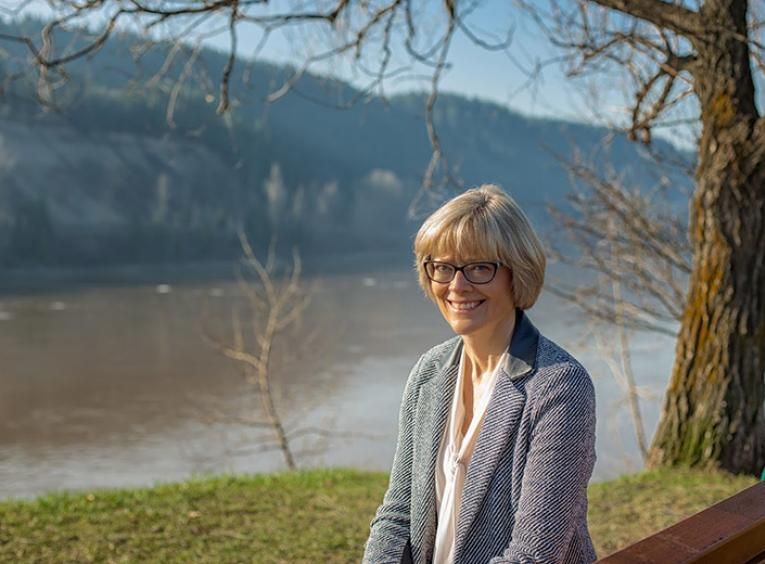 A smiling woman sits on a bench above a river.