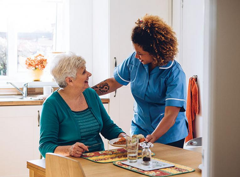 Home support worker stands at dinner table next to elderly woman
