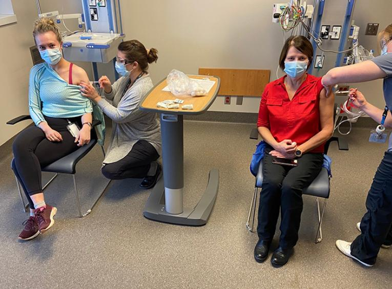 Two women are sitting in a hospital setting receiving vaccinations from nurses.